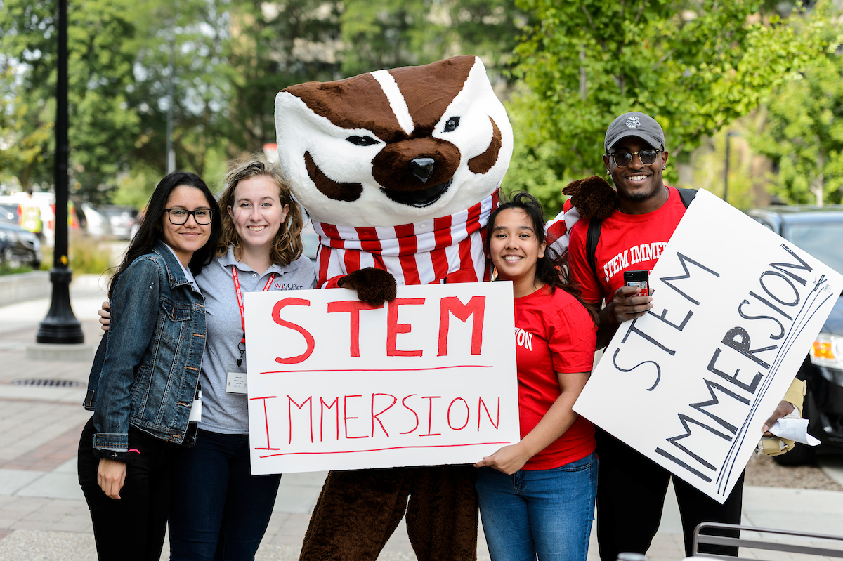 Bucky Badger mascot holing sign that reads STEM IMMERSION