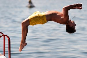 Student diving off of pier into Lake Mendota