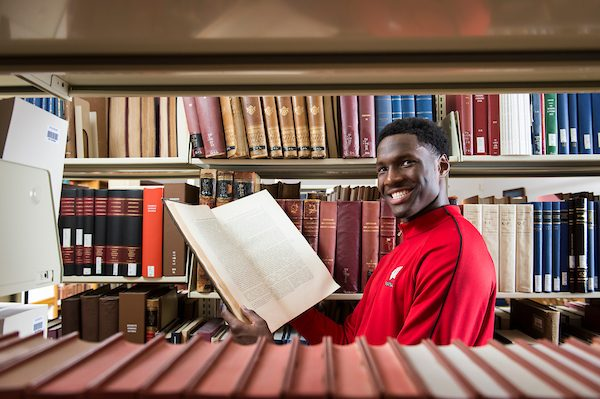 Badger men's basketball player Nigel Hayes browses book in Memorial Library